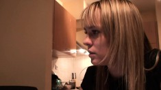 Blonde is watching an old party on her computer and makes something to eat