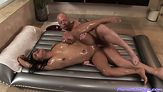 Sexy brunette uses her tiny body to oil up a man before fucking